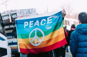 Person holding a rainbow flag with the word peace written on it at a larger gathering