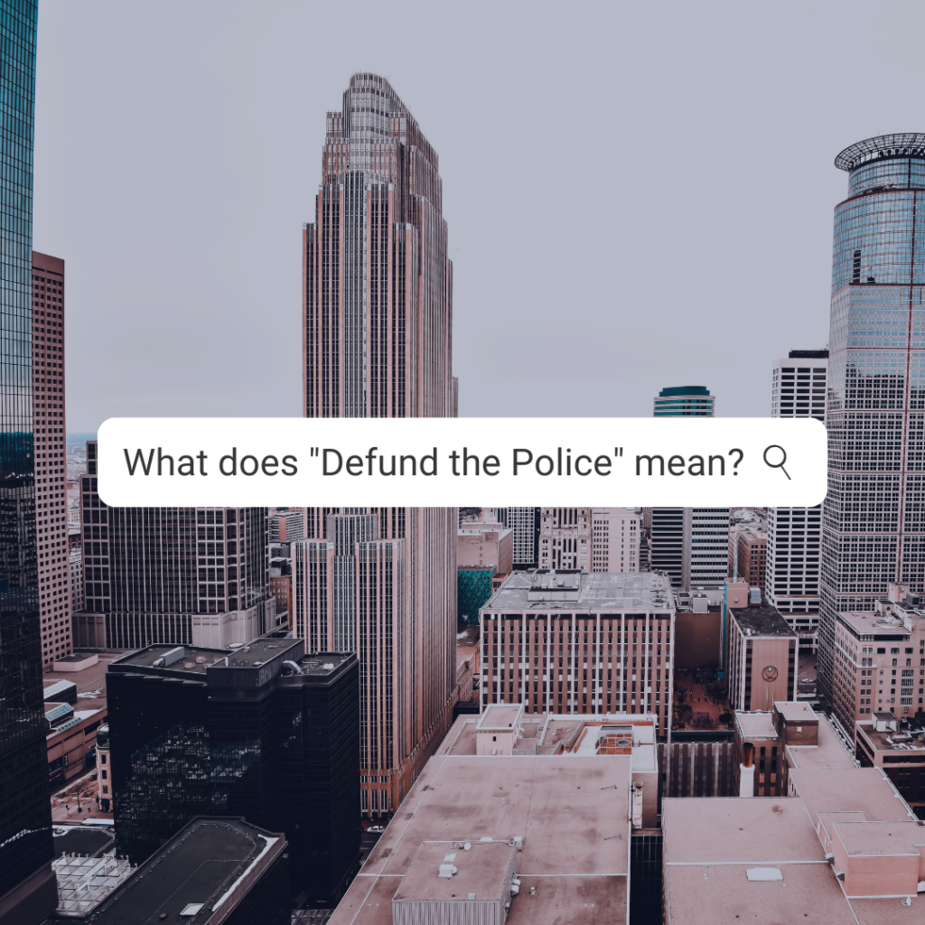 """A photograph of downtown Minneapolis with the test """"What does defund the police mean?"""""""